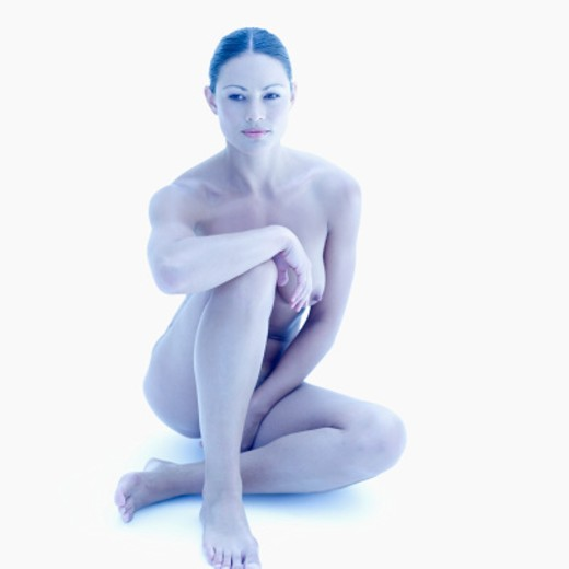 Nude young woman sitting on the floor : Stock Photo