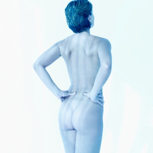 Stock Photo: 1491R-1102158 Rear view of a nude young woman standing with her hands on her back