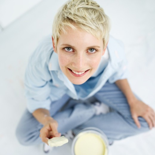 Stock Photo: 1491R-1102159 Elevated view of a young woman holding a paint brush over a can of paint
