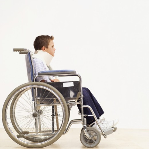 Stock Photo: 1491R-1102467 Young boy (8-10) in a wheelchair wearing a neck brace