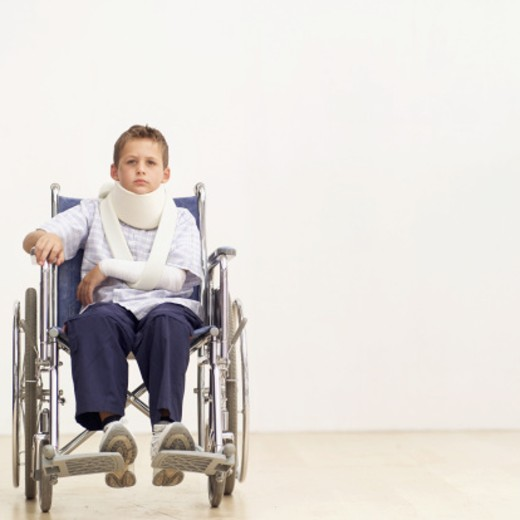 Portrait of a young boy (8-10) in a wheelchair wearing a neck brace : Stock Photo