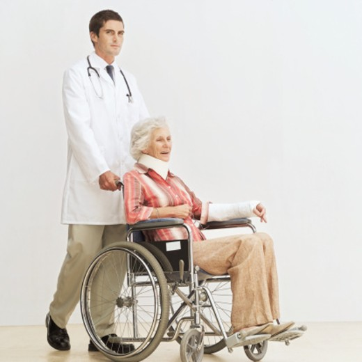 Stock Photo: 1491R-1102501 Young male doctor pushing an old woman in a wheel chair