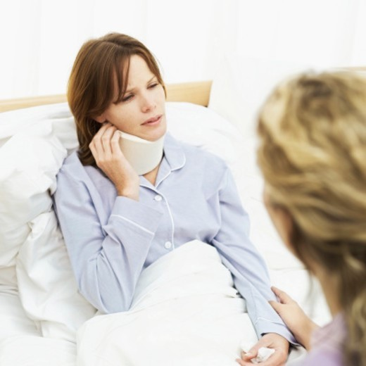 Young woman sitting on the edge of a bed talking to a sick Young woman : Stock Photo