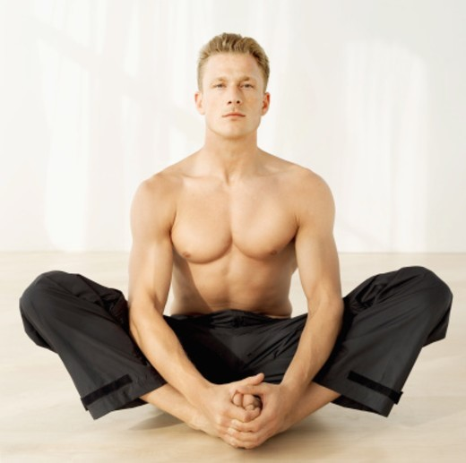 Stock Photo: 1491R-1103300 Portrait of young man practicing yoga on the floor