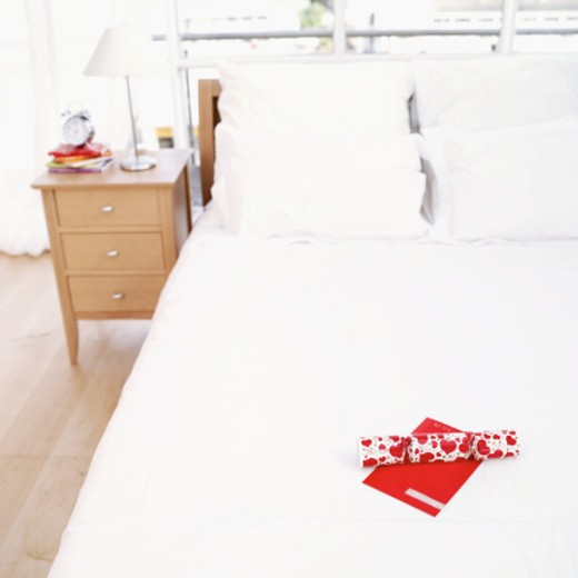 Stock Photo: 1491R-1103391 Elevated view of a gift and valentine card lying on a bed