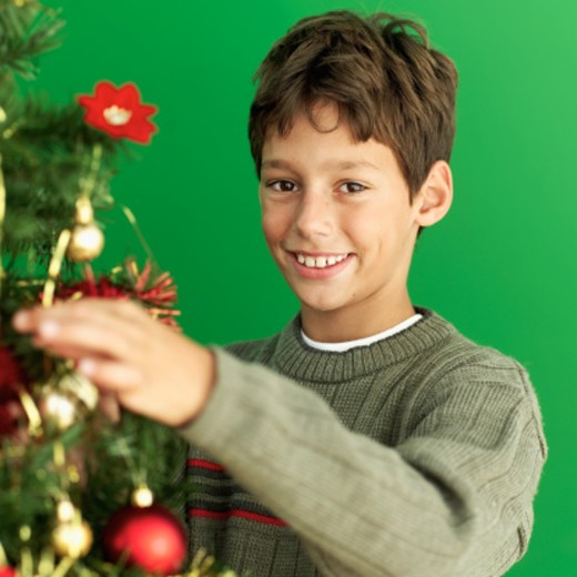 Portrait of a young boy (10-11) smiling and decorating a Christmas tree : Stock Photo