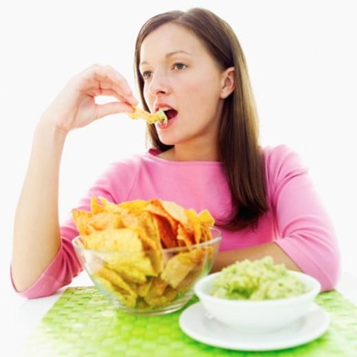 Stock Photo: 1491R-1104177 Teenage girl (15-17) eating a nacho with dip