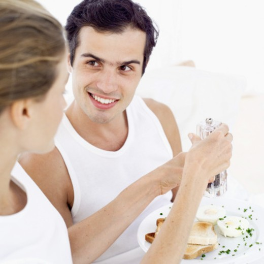 Stock Photo: 1491R-1104273 Young woman crushing pepper on a plate of eggs in a young man's hands