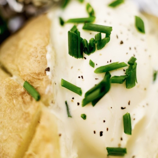 Close-up of a baked potato with sour cream : Stock Photo