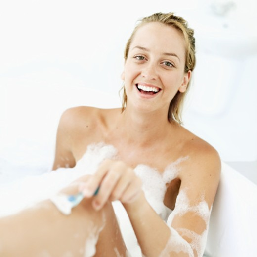 Stock Photo: 1491R-1104768 Young woman shaving her leg in a bubble bath