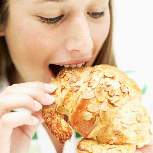 Close-up of a teenage girl (15-17) eating a croissant : Stock Photo