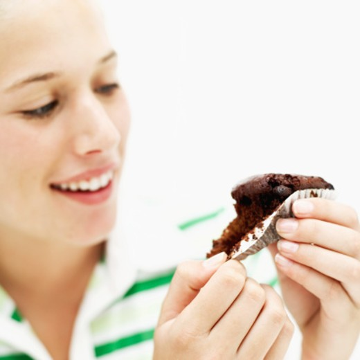 Close-up of a teenage girl (15-17) removing a muffin from a wrapper (blurred) : Stock Photo