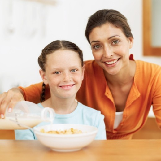 Stock Photo: 1491R-1105036 Young mother pouring milk from a bottle into a young girl's (8-10) bowl of cereal