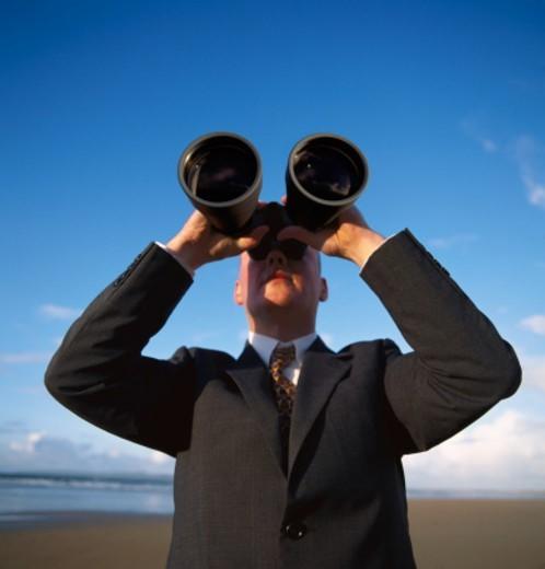 close-up of a man looking through binoculars : Stock Photo