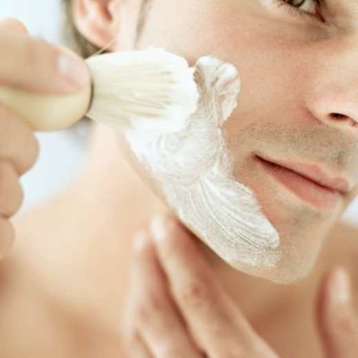 Close-up of a young man foaming his face with a shaving brush : Stock Photo