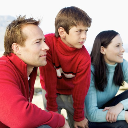 Side profile of a young couple on the beach with their son (10-12) : Stock Photo