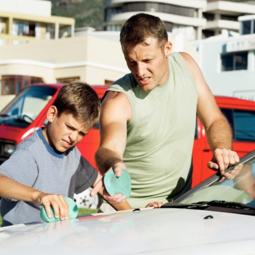 Stock Photo: 1491R-1105633 Young man instructing his young son on car washing