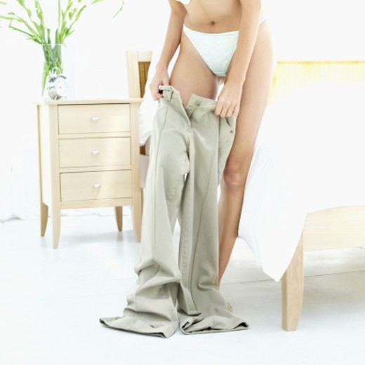 Close-up of a young woman putting on pants in bedroom : Stock Photo