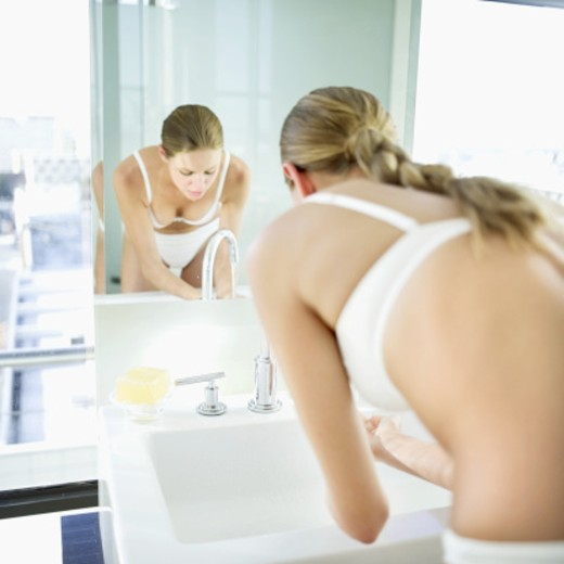 Stock Photo: 1491R-1106691 Young woman standing in underwear washing hands in washbasin