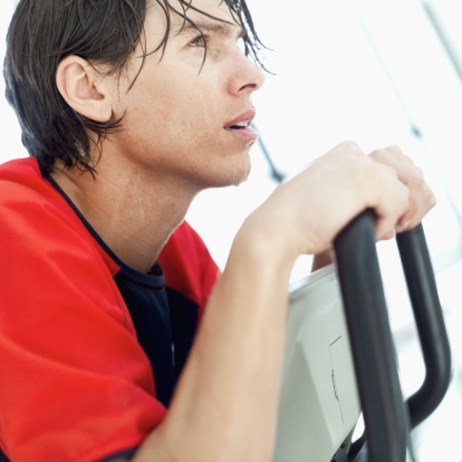 Stock Photo: 1491R-1107077 Side profile of a young man exercising on a machine