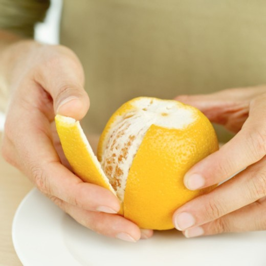 Stock Photo: 1491R-1107164 Close-up of a man's hands peeling an orange