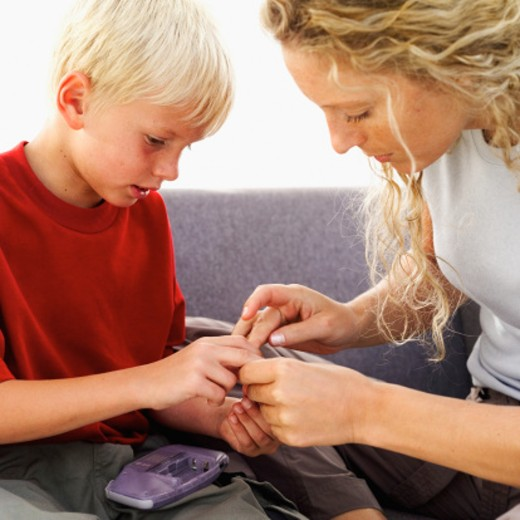 Young woman and young boy (10-11) fixing component of videogame : Stock Photo