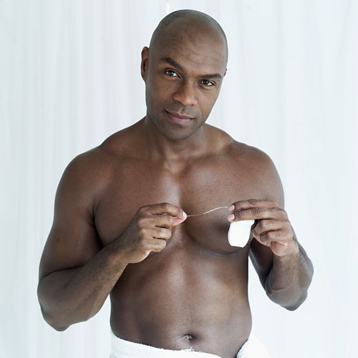 Portrait of a bare-chested young man holding dental floss in hands : Stock Photo