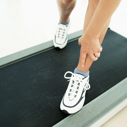 Stock Photo: 1491R-1107697 Woman touching her leg while standing on treadmill