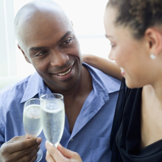 A young couple toasting with champagne : Stock Photo