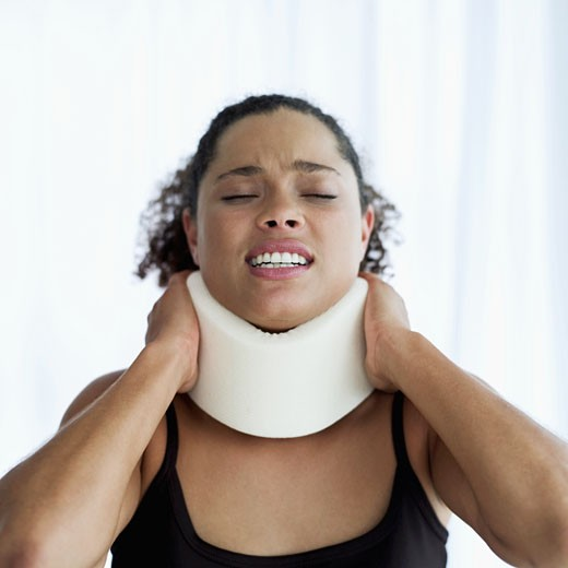 Young woman wearing a neck brace : Stock Photo