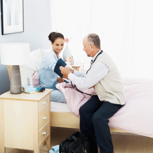 Stock Photo: 1491R-1108509 A male doctor taking the blood pressure of a young woman lying in bed using a blood pressure gauge
