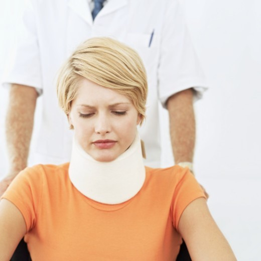 Close-up of a young woman wearing a neck brace and sitting in wheelchair with doctor pushing her : Stock Photo