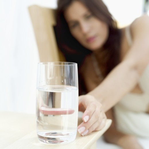 Stock Photo: 1491R-1108748 Young woman reaching out for a glass of water