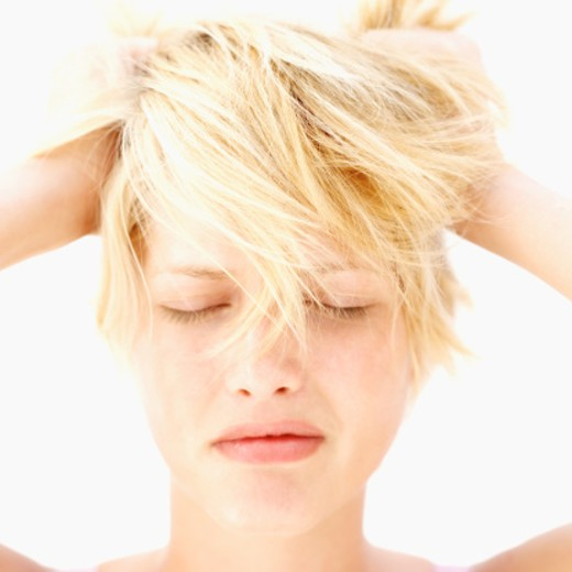 Close-up of a young woman holding up her hair : Stock Photo
