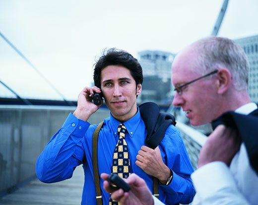 Two businessmen standing outdoors talking on a mobile phone and operating a beeper : Stock Photo