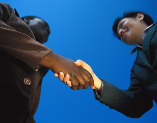 Stock Photo: 1491R-1110895 Low angle view of two young businessmen shaking hands outdoors