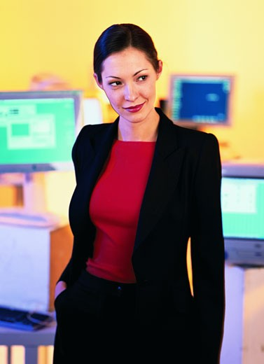 Young businesswoman standing and smirking : Stock Photo