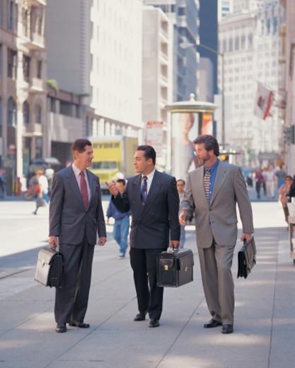 businessmen walking talking on a city sidewalk : Stock Photo