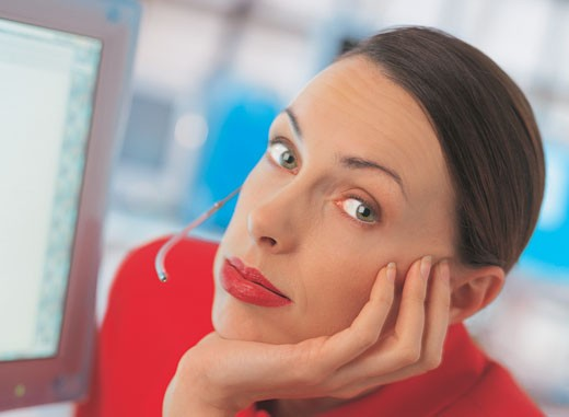 close-up of a woman wearing a headset looking bored at work : Stock Photo