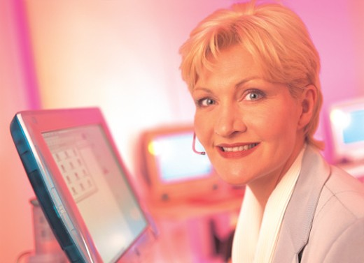 portrait of a woman wearing a headset sitting across a computer screen (infrared) : Stock Photo