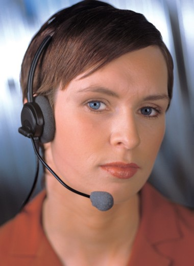 portrait of a woman wearing a telephone headset : Stock Photo