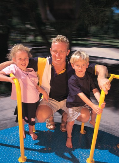 Stock Photo: 1491R-1112686 portrait of a father and his children on a merry-go-round