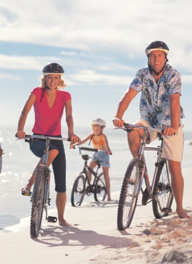 family riding bicycles on the beach : Stock Photo