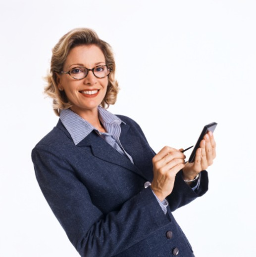 Stock Photo: 1491R-1113005 portrait of a young woman standing and using a hand held device