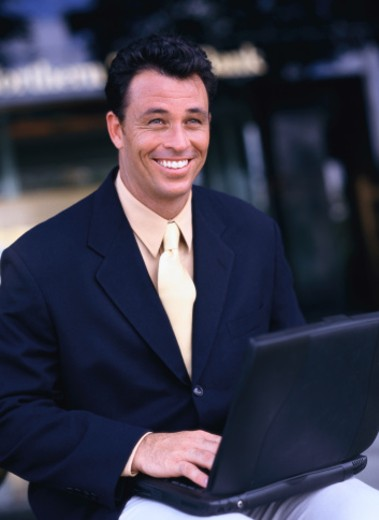portrait of a businessman smiling with a laptop computer on his lap : Stock Photo