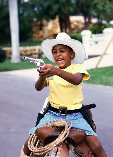 portrait of a young boy (6-8) dressed as a cowboy with a toy gun : Stock Photo
