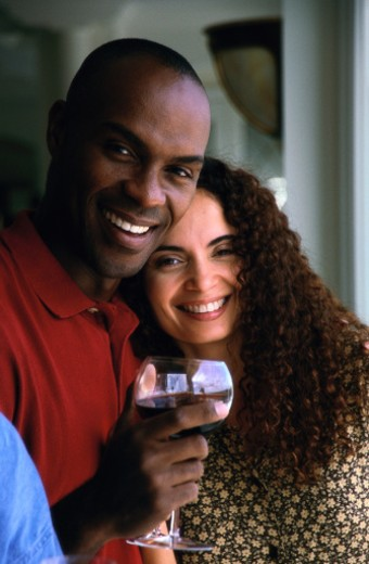 portrait of man holding a glass of red wine with a woman beside him : Stock Photo