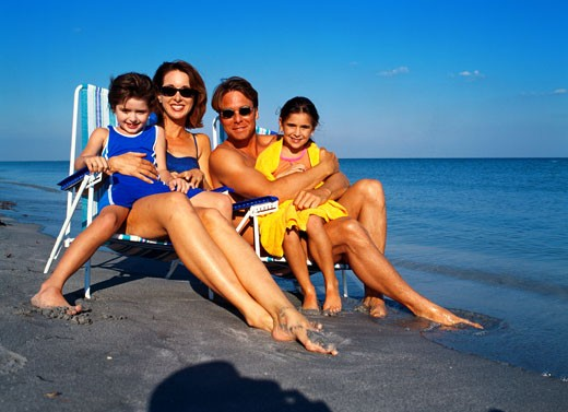 portrait of a family sitting on chairs at a beach : Stock Photo