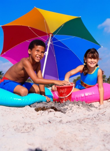 two young children sitting on flotation tubes playing with sand on the beach : Stock Photo