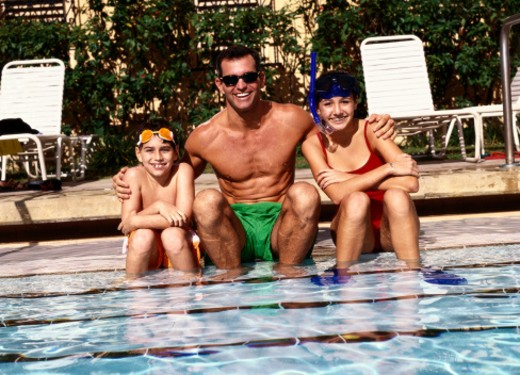 Stock Photo: 1491R-1114232 portrait of a family sitting in a swimming pool smiling